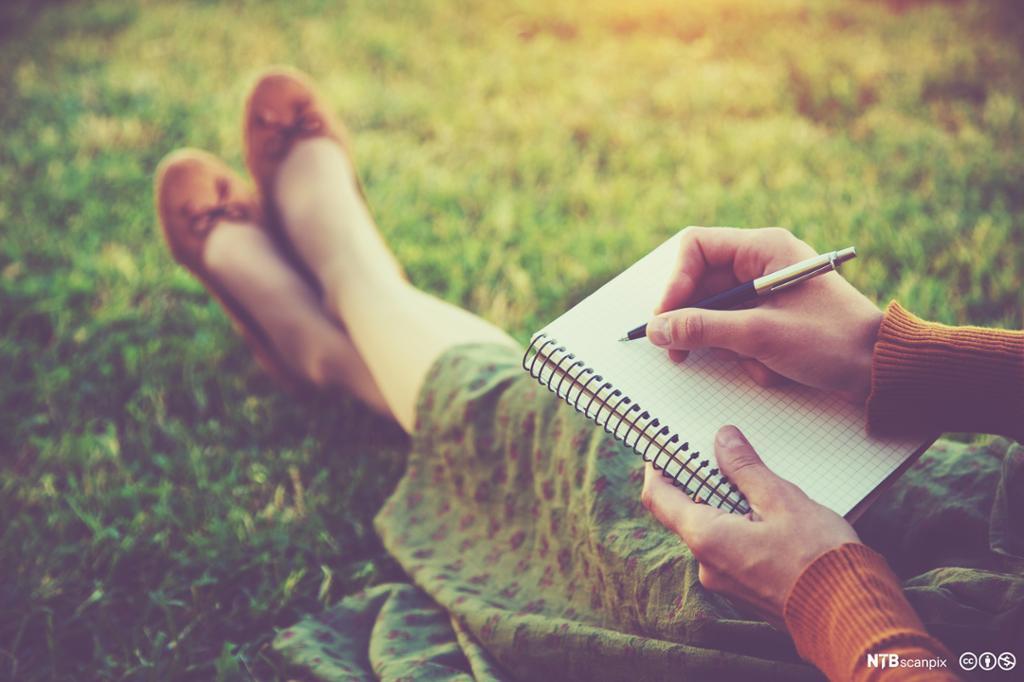 En kvinne sitter i en park og skriver på en blokk. Foto.