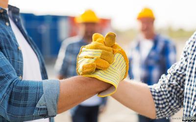 To bygg- og anleggsarbeidere  med arbeidshansker håndhilser. Foto.