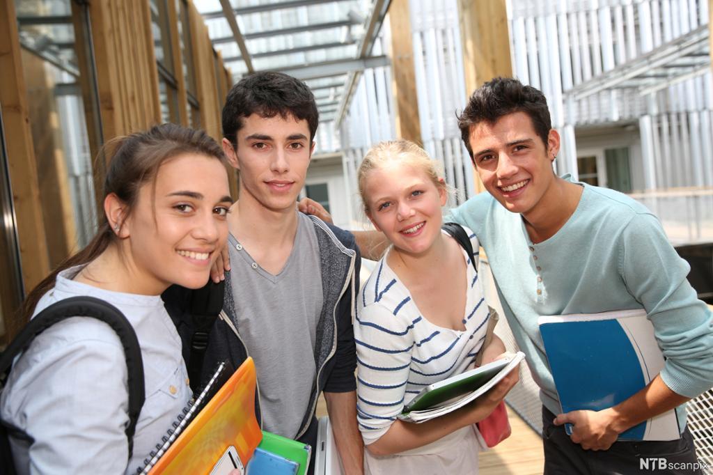 Fire ungdommar med skulebøker i gangen på skulen. Bilete.