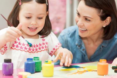 Jente maler. en kvinne sitter ved siden av og smiler til jenta. Young girl painting. Mother and daughter using paints. Foto.