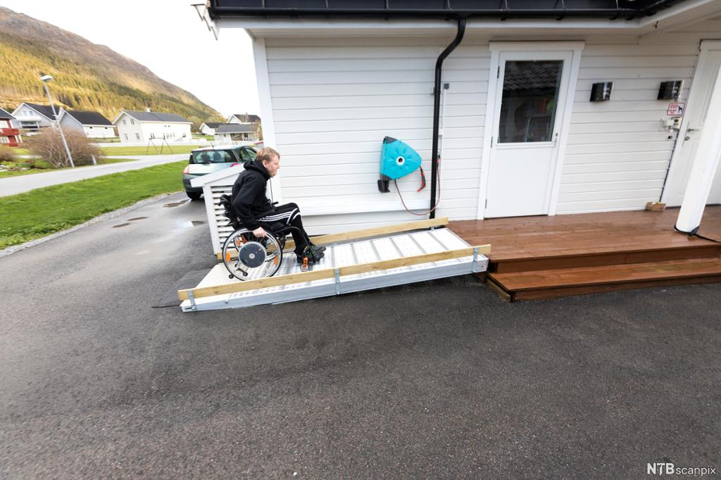 Rullestolbruker som kjører på rullestolrampe ved huset sitt. Foto.