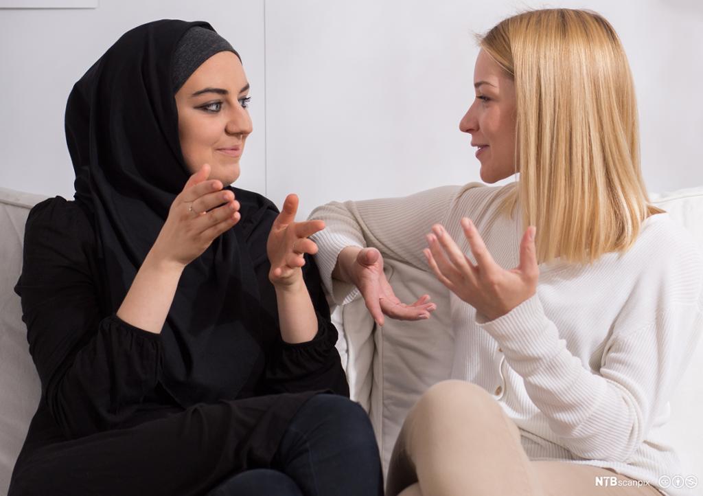 Jente med hijab samtaler med blond langhåret jente. Foto