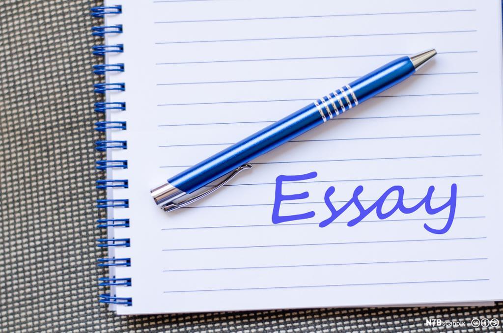 Skriveblokk og penn. Ordet essay skrevet med håndskrift. Foto.
