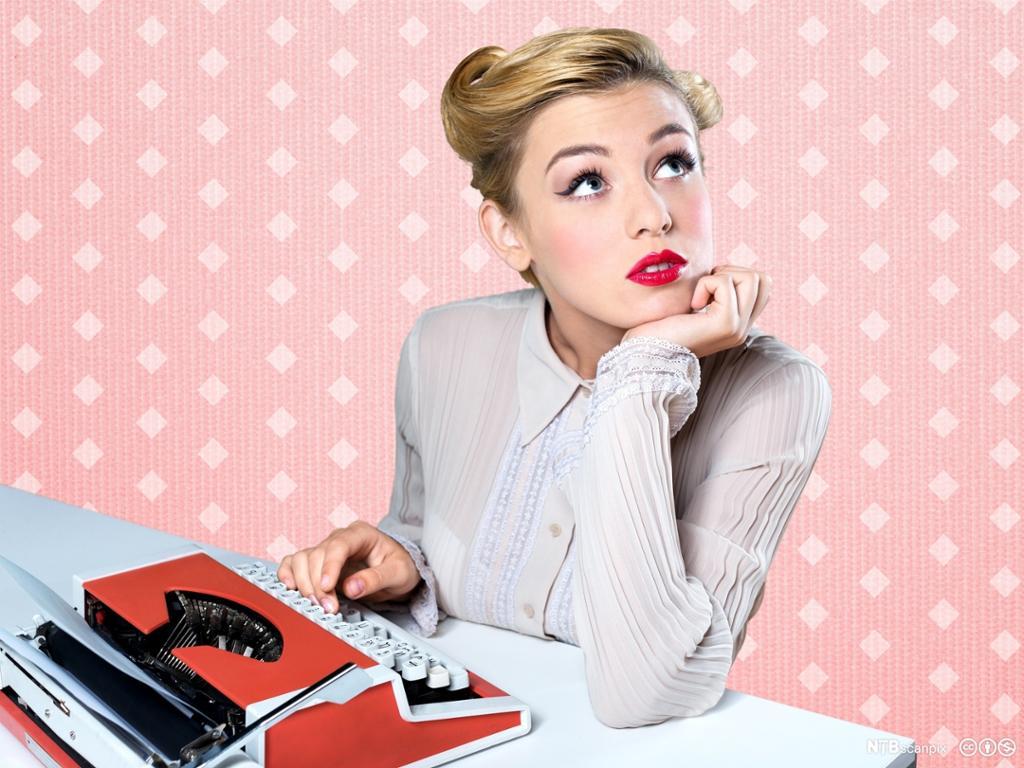 Retrobilde av kvinne med skrivemaskin.Rosa bakgrunn. Fotografi.