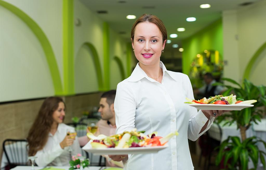 En servitør med to tallerkener i hendene. Foto.