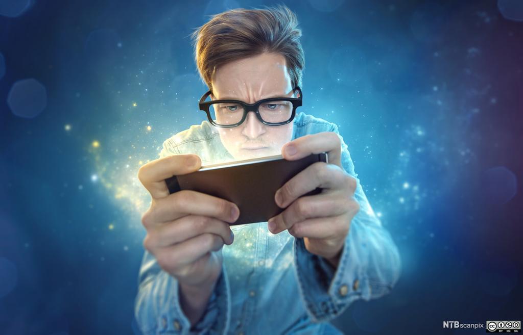 Nerd som spiller på mobilen. Foto.