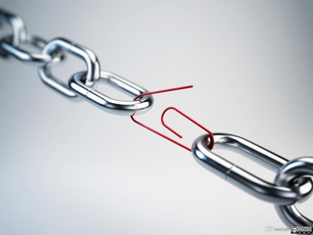 En rød binders er brukt som et ledd i en metallenke.Foto.