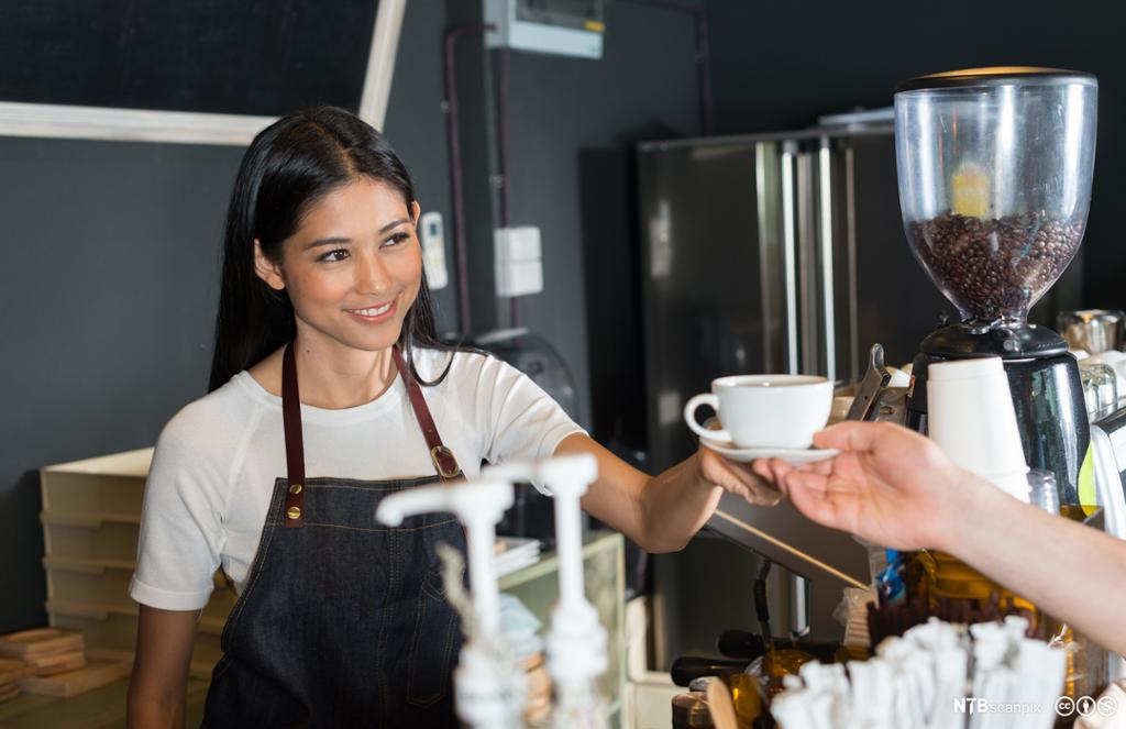Ekspeditør serverer en kaffekopp