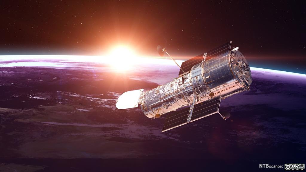 Hubble-teleskopet med jorda og sola i bakgrunnen. Foto.