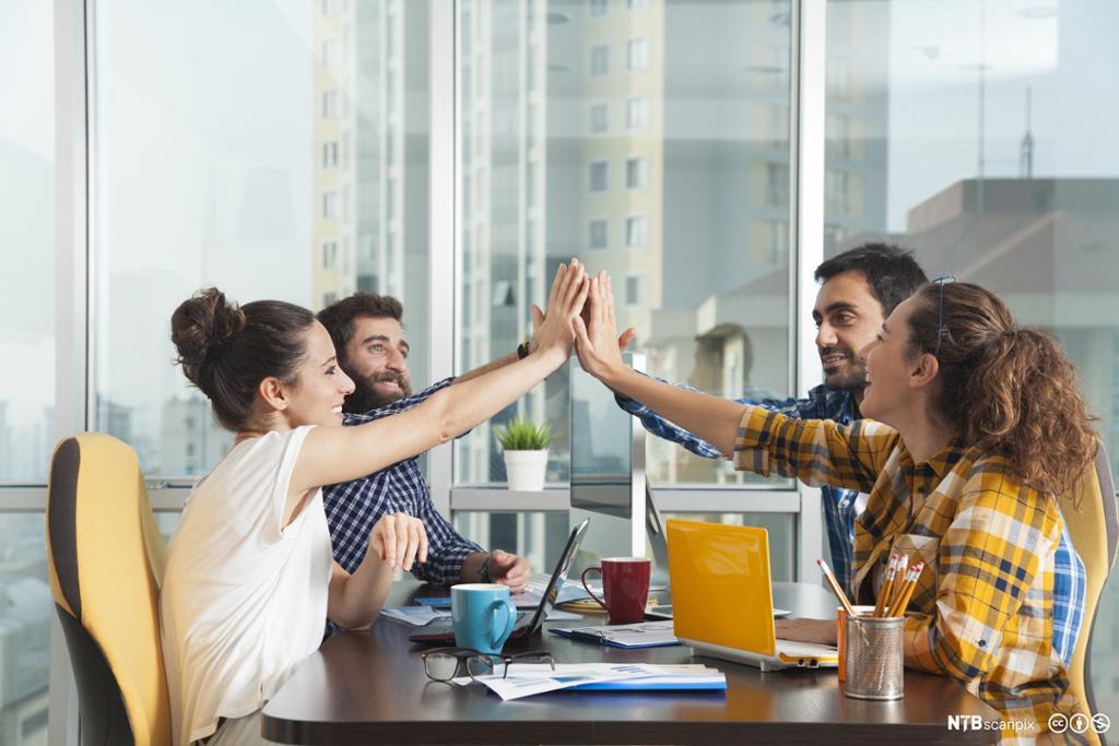 Fire stykker som gir hverandre en high five. Foto.