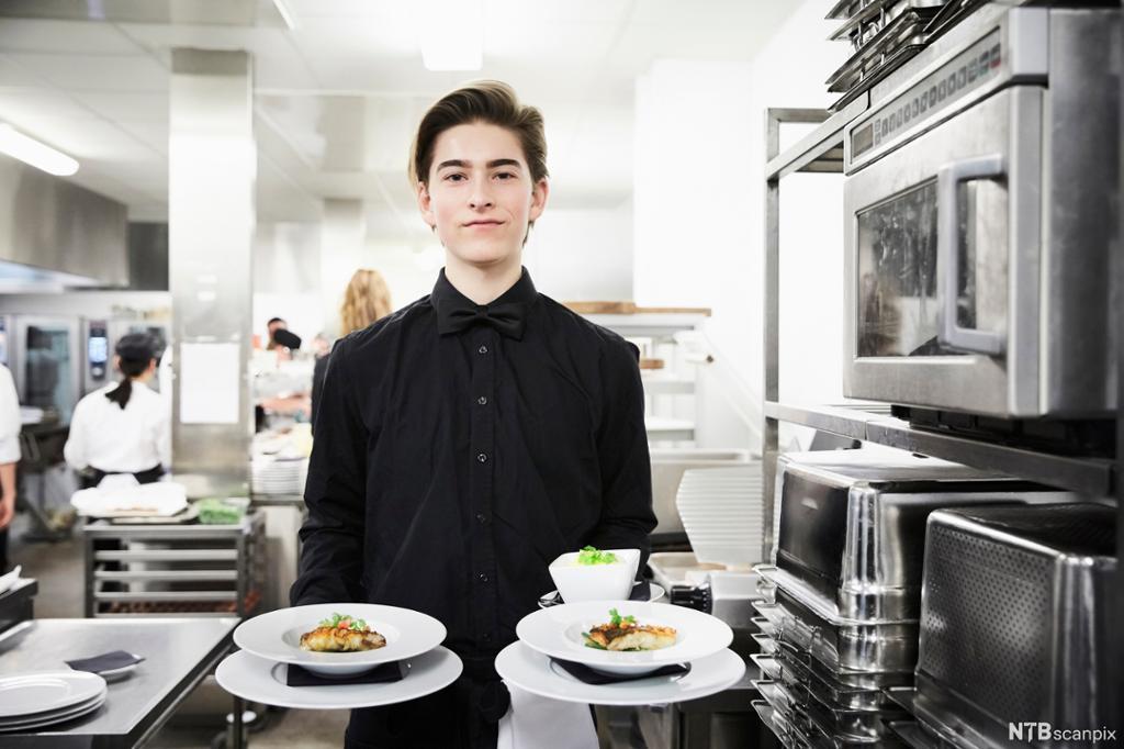 En servitør som holder to tallerkener. Foto.