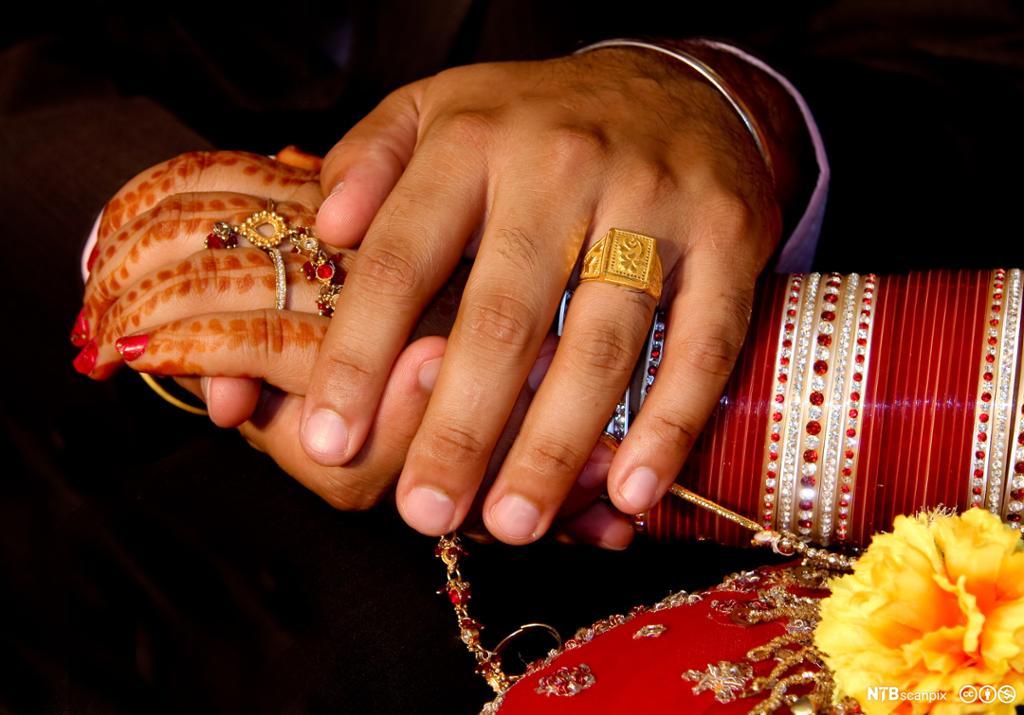 Hånden til en mann over en dekorert kvinnehånd. Foto.