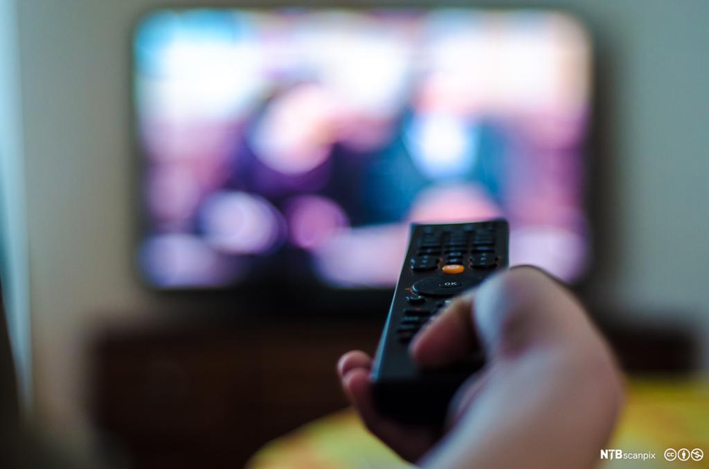 En hånd trykker på en kontroll for å velge TV-kanal. Bilde.