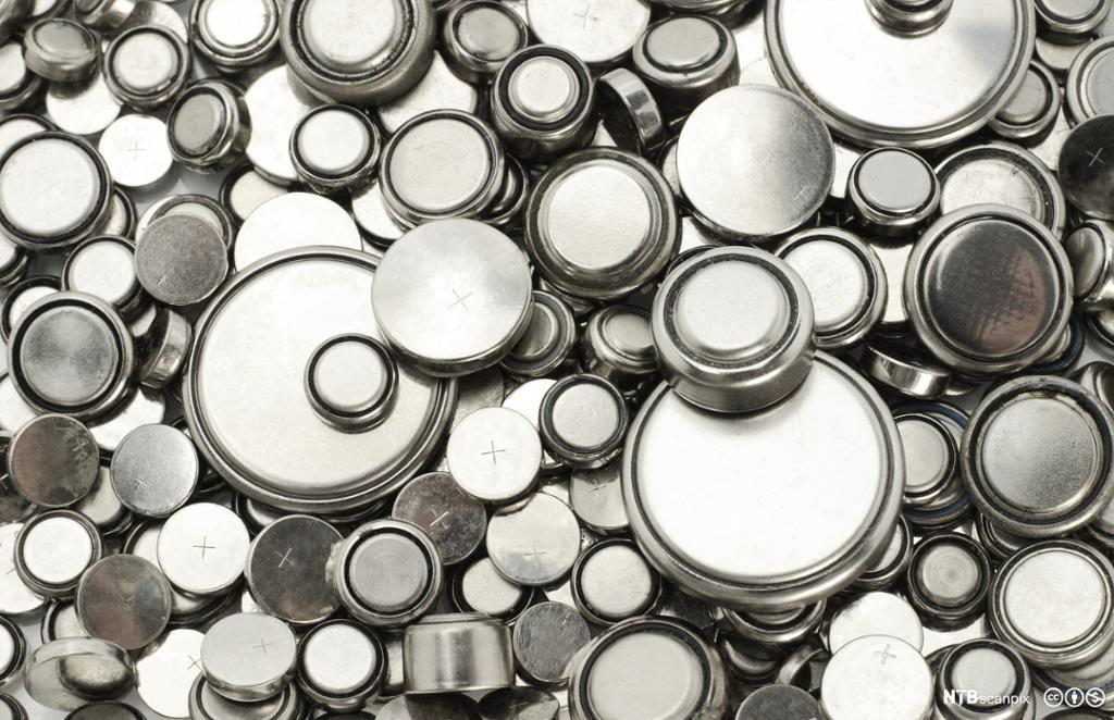 Store og små knappecellebatterier ligger spredt utover og fyller hele bildet. Foto.