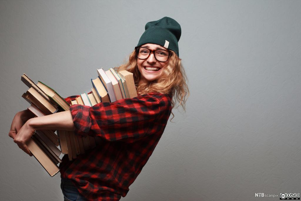 Bilde av en jente som bærer på en stor stabel med bøker. Foto.