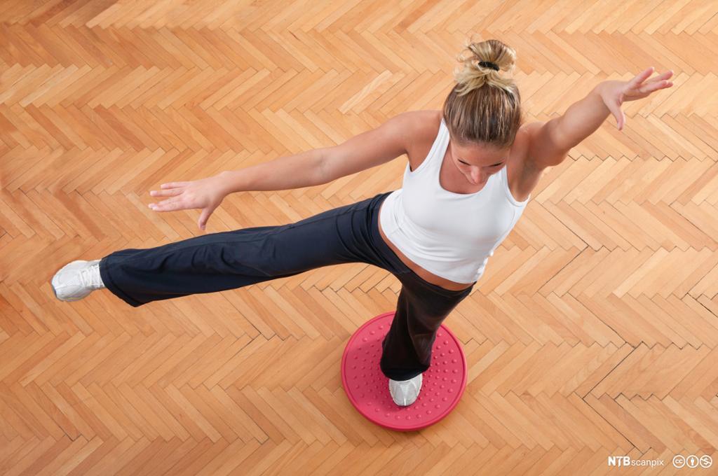 Kvinnelig idrettsutøver trener på en balanseplate. Foto.