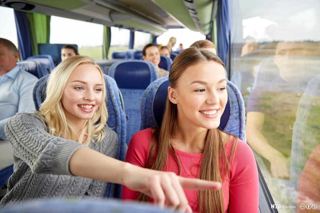 To unge kvinner sitter i en sightseeingbuss. Foto.