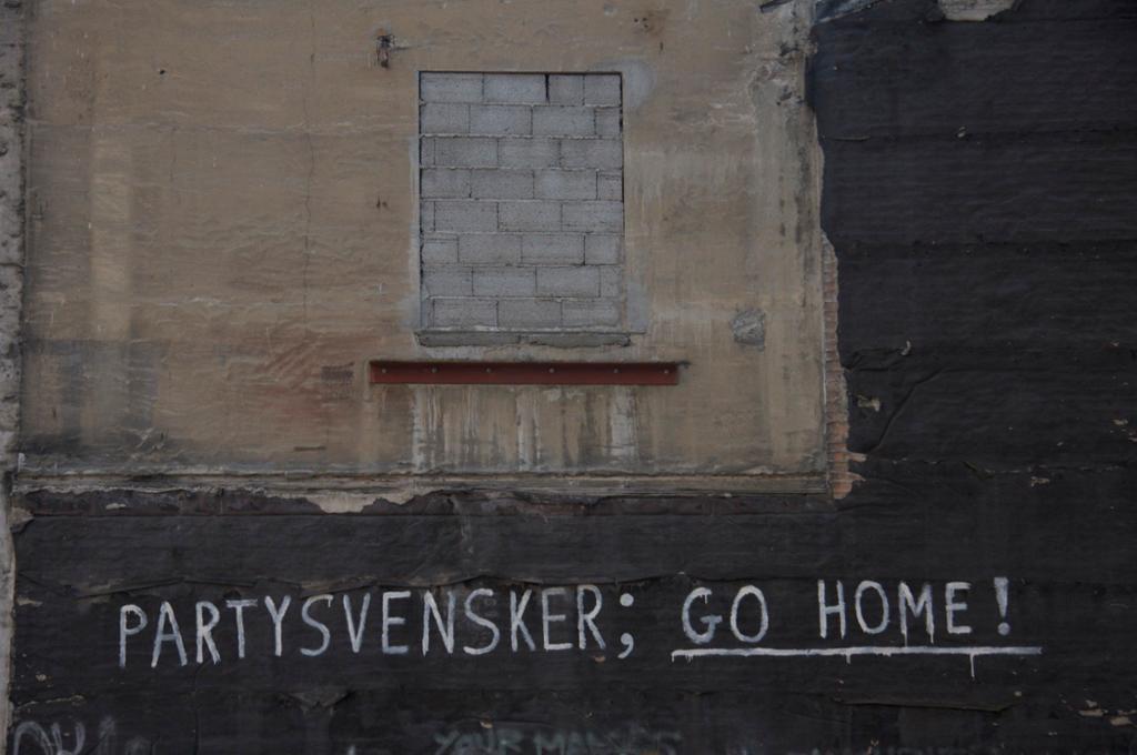 Murvegg med en tagget tekst som sier Partysvensker; go home! Foto.
