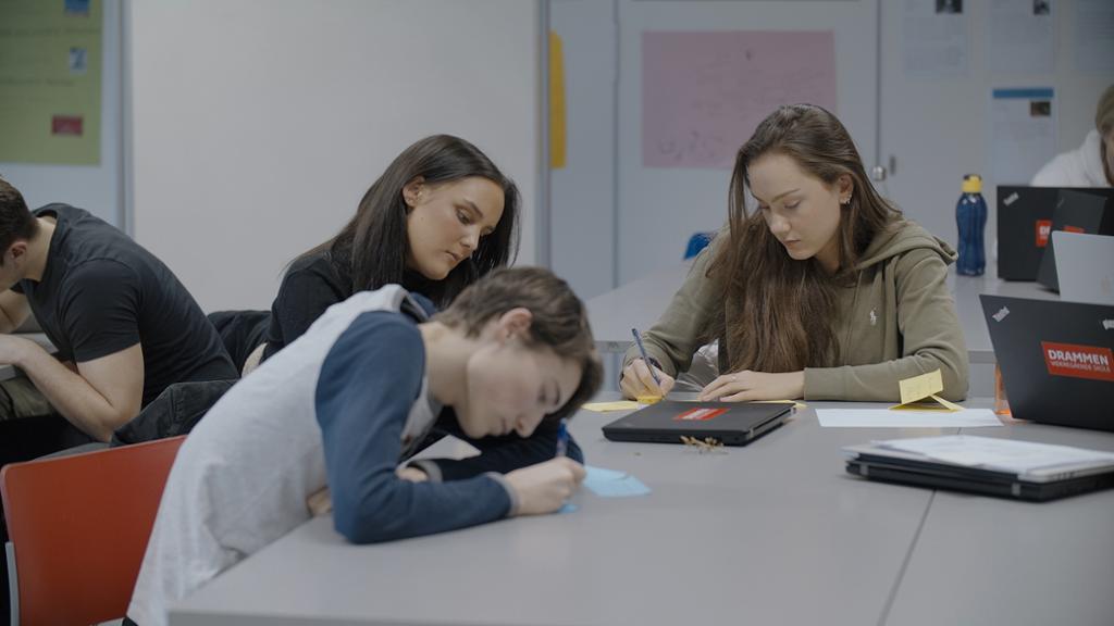 Tre elever sitter rundt et bord og noterer. De utfører kreativitetsøvelsen brainstorming. Foto.