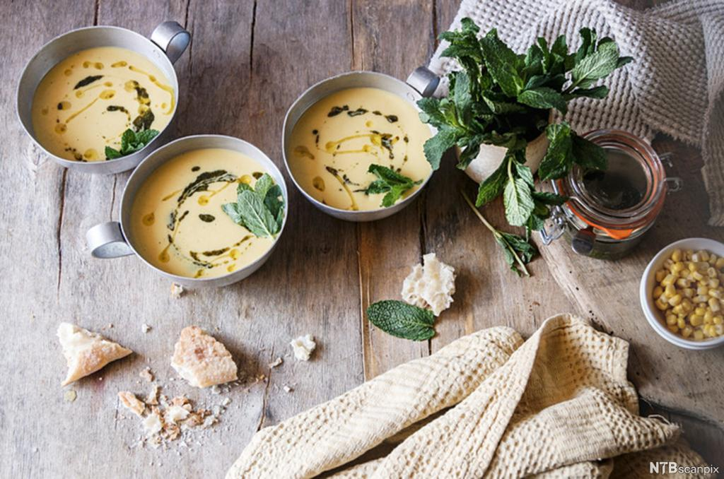 Tre skåler kremet, lys suppe, sammen med brødbiter og mais på et bord. Foto.