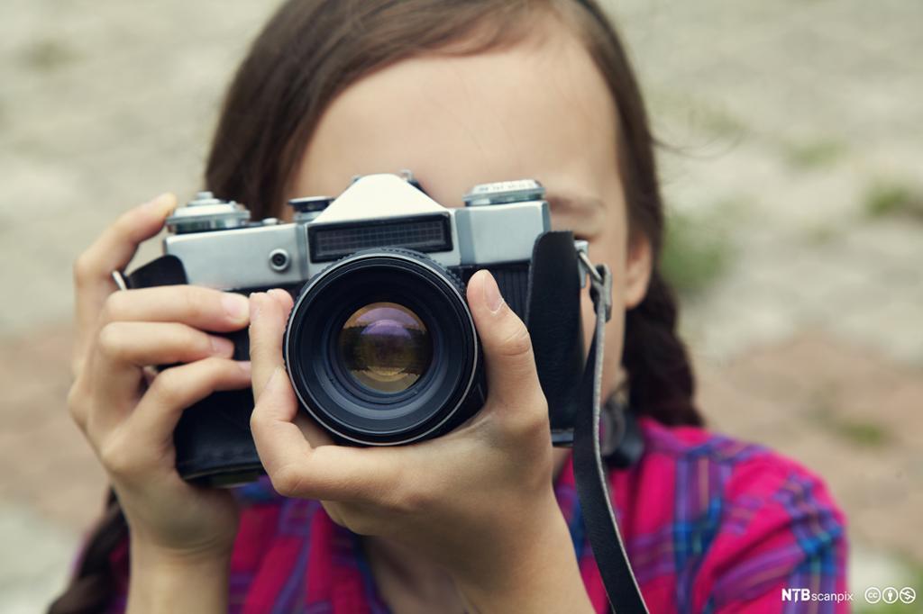 To hender som holder et fotoapparat. Fotografi.
