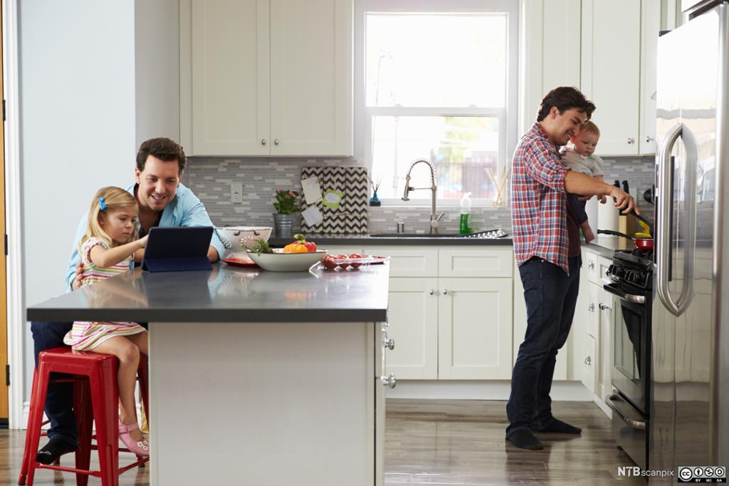 Fedre lager mat sammen med to små barn. Foto.