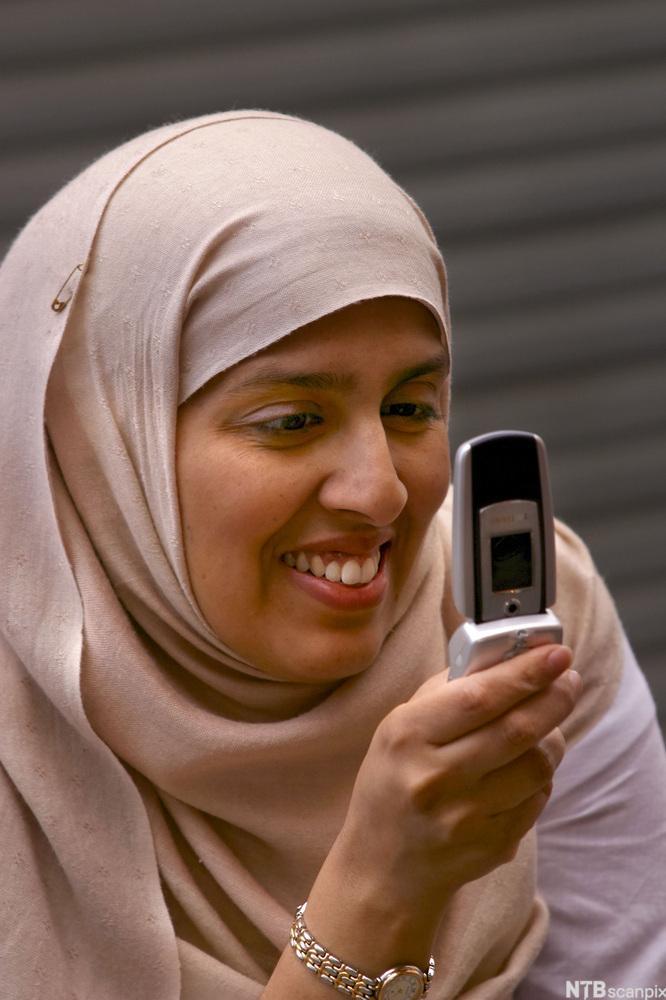 kvinne med hijab, som bruker mobiltelefon.Foto