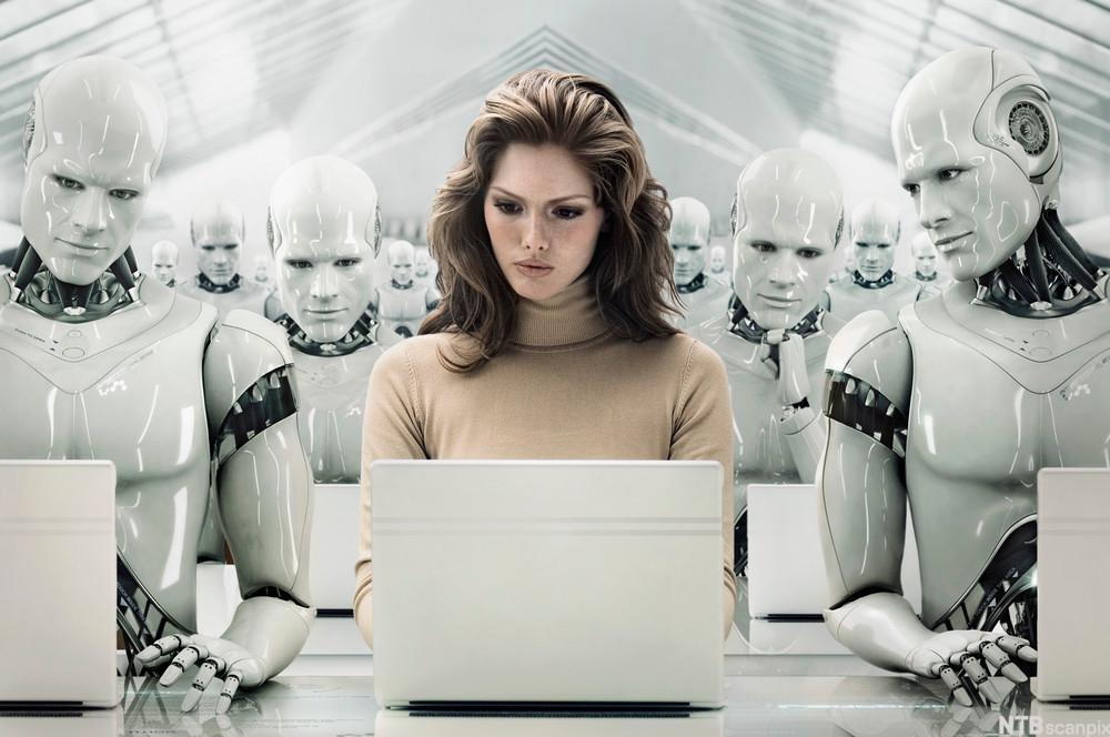 Kvinne med laptop omgitt av roboter. Foto.