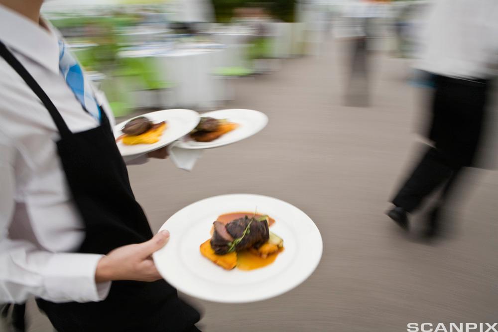 Servitør serverer mat. Foto.