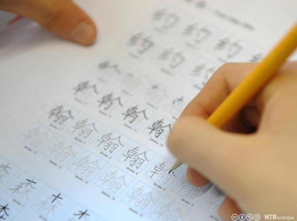 En som øver seg på å skrive kinesiske tegn. Foto.