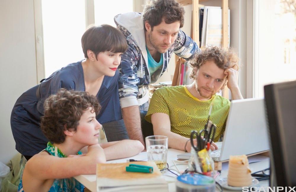 En mann viser tre andre noe på en laptop. Foto.