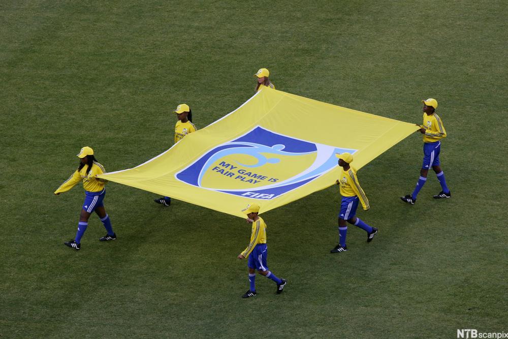 Flaggbærere på en idrettsarena. Foto.