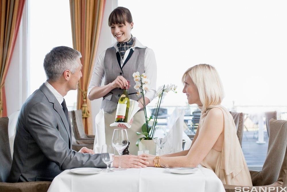 Servitrise serverer vin til eit par. Foto.