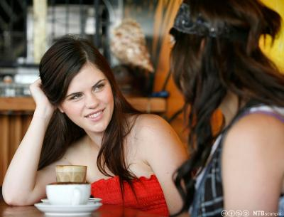 To unge kvinner drikker kaffe sammen på kafé. Foto.