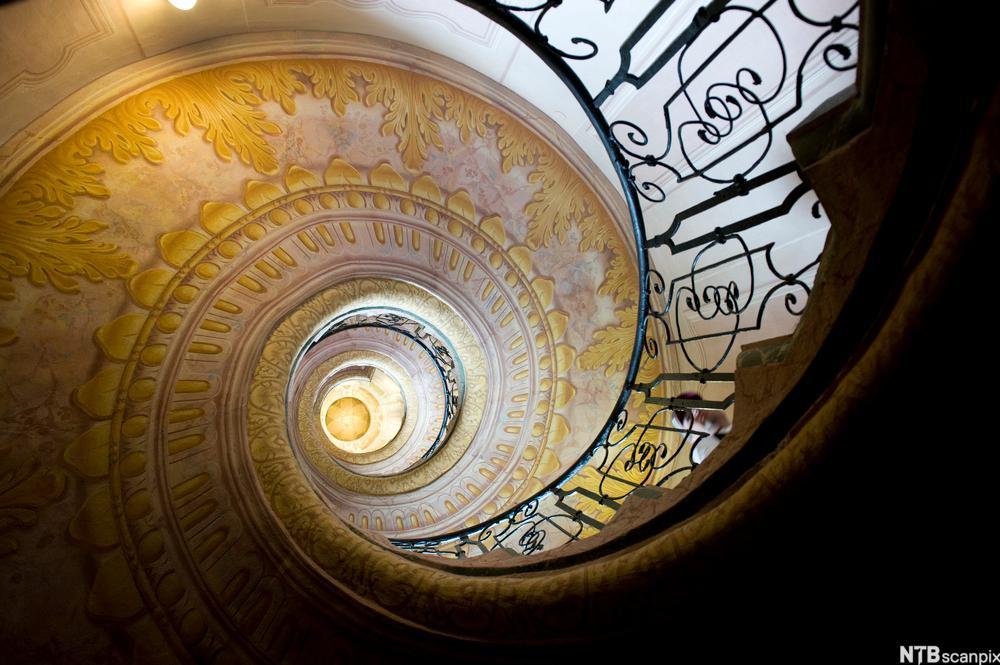 Spiraltrapp med barokke gelender og dekor, sett i froskeperspektiv. Foto.