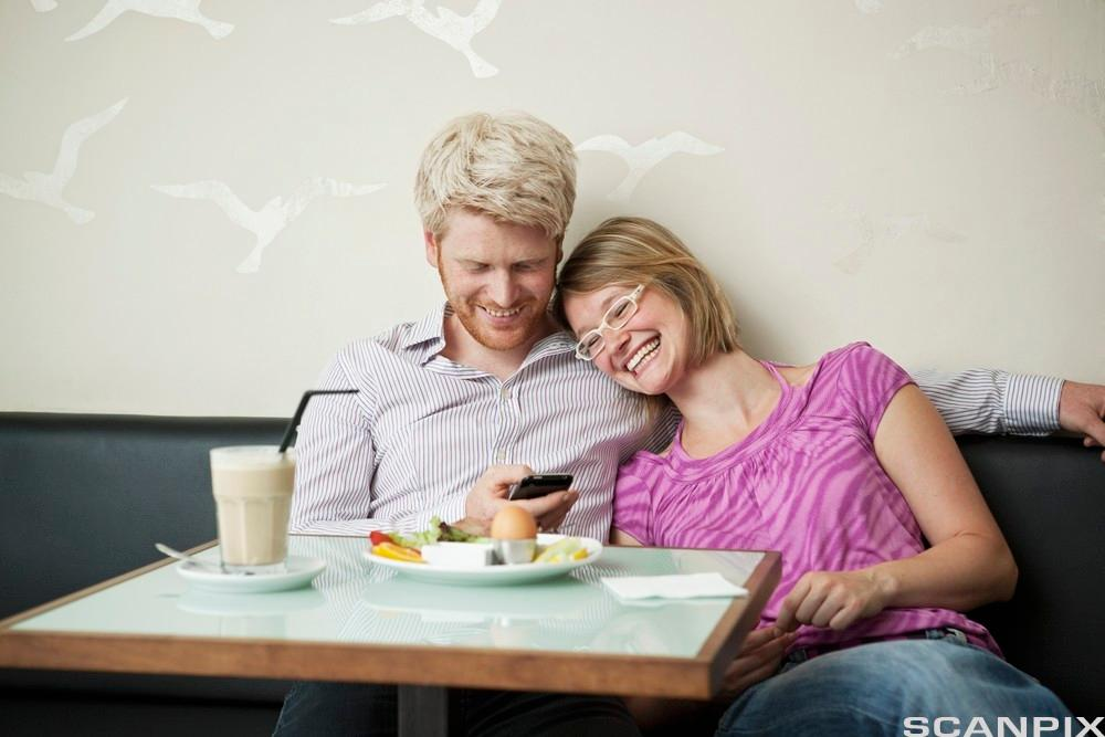 Fornøyd ungt par på restaurant. Foto.