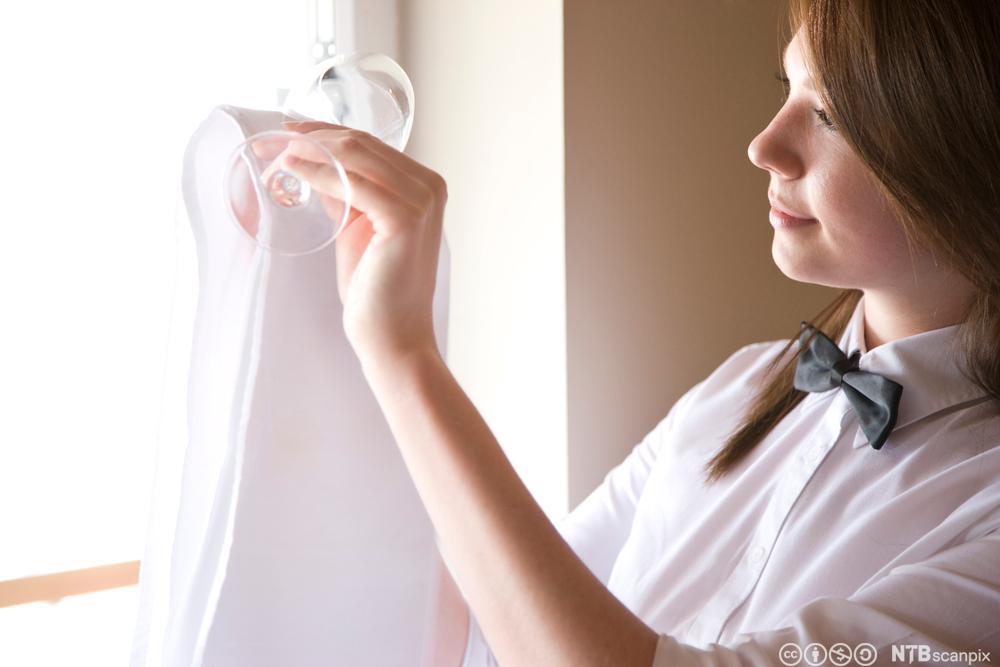 En servitør holder et vinglass mot vinduet for å sjekke om det er rent. Foto.