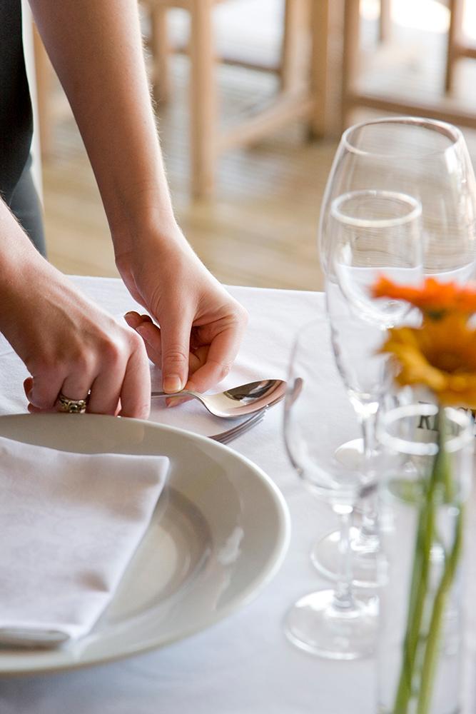 Servitør dekkjer bordet. Foto.