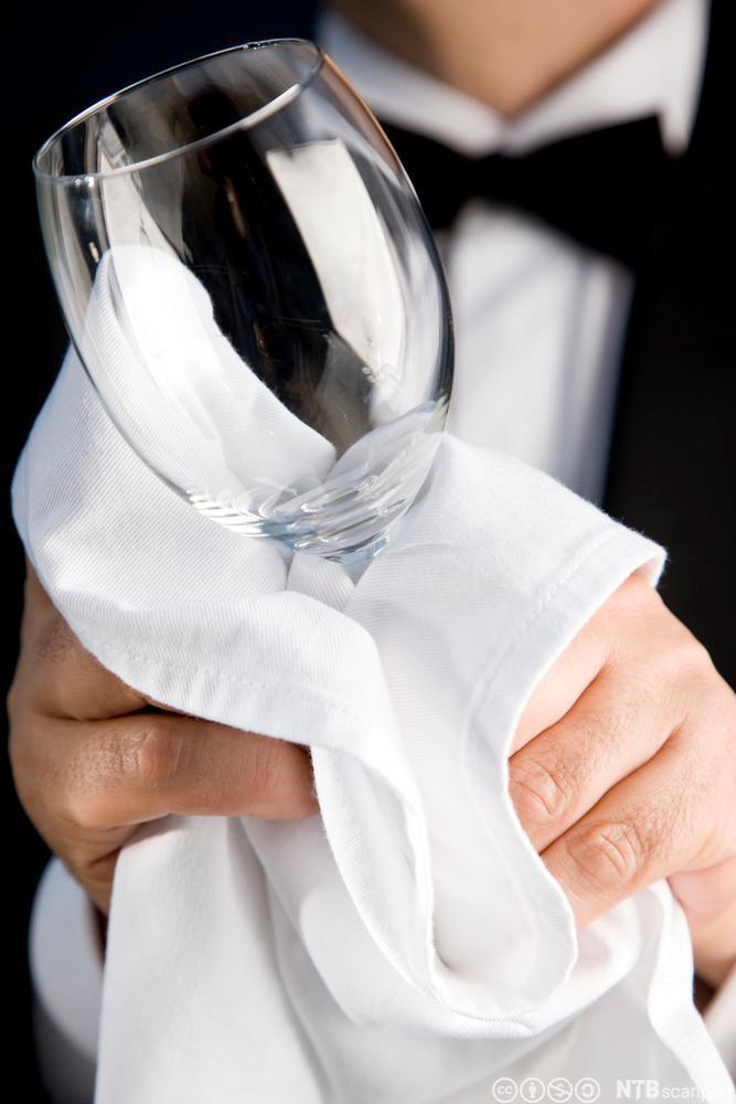 Ein servitør polerer eit vinglas. Foto.