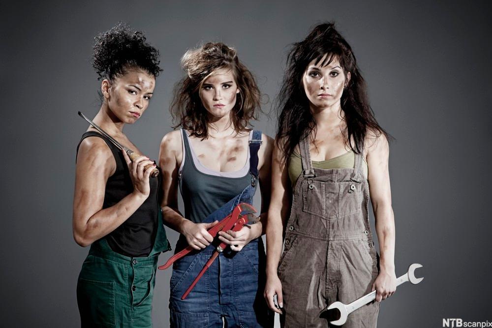 tre kvinner i kjeledress med verktøy