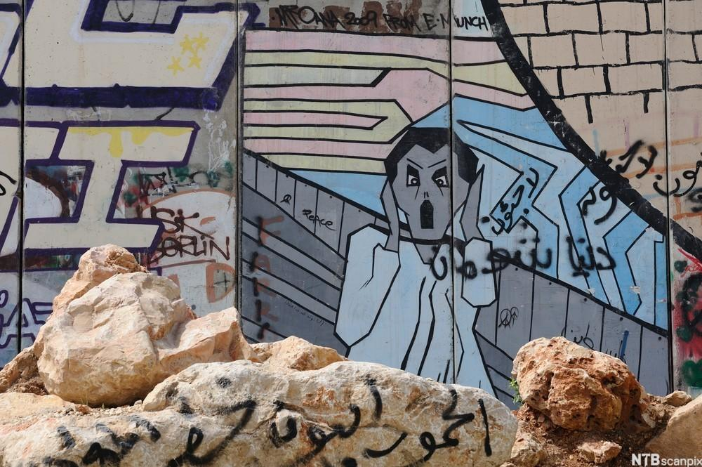Bilde med skrikmotiv malt på muren som skiller Israel fra Palestina.