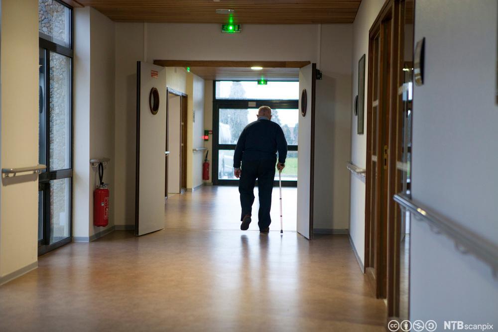 En person går nedover en korridor. Foto.
