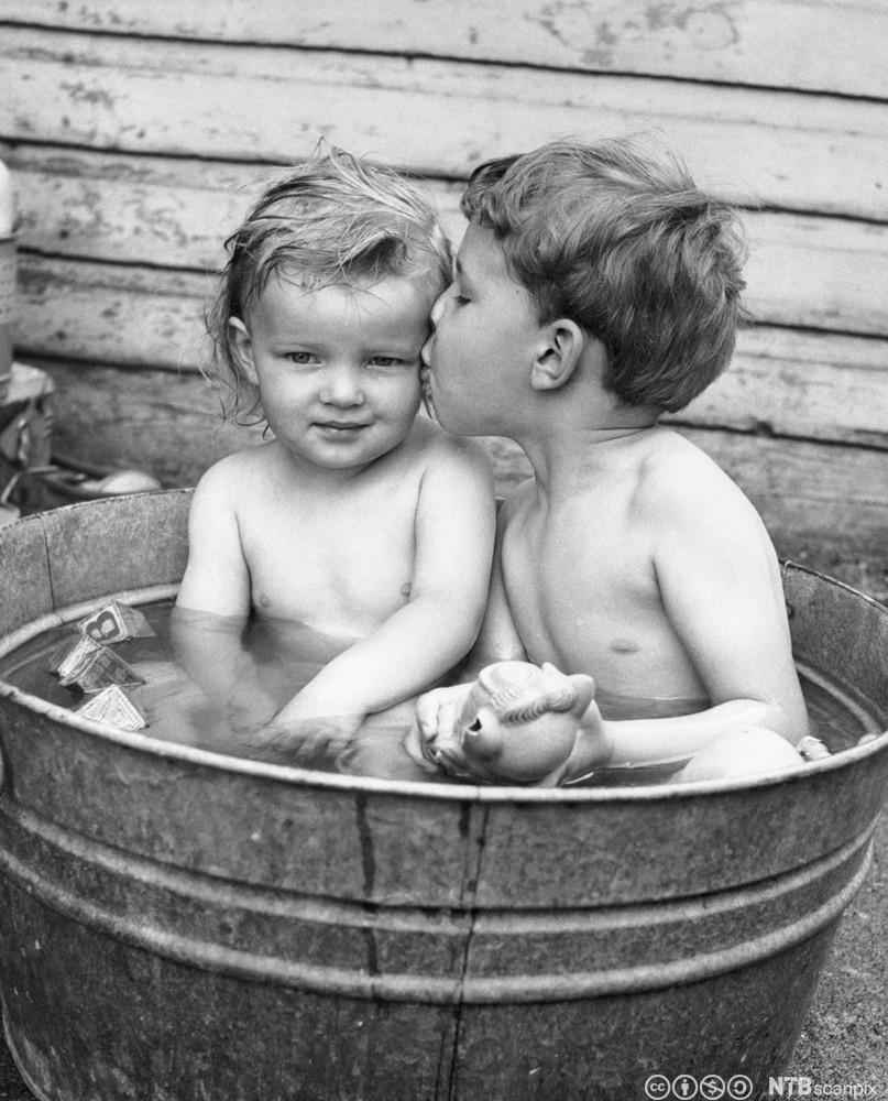 Bror og syster badar i ein badestamp. Foto.