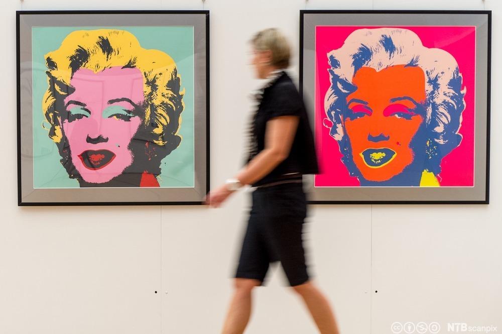 Fra en Andy Warhol-utstilling i Tyskland. En kvinne går forbi to av Warholds bilder av Marilyn Monroe. Foto.