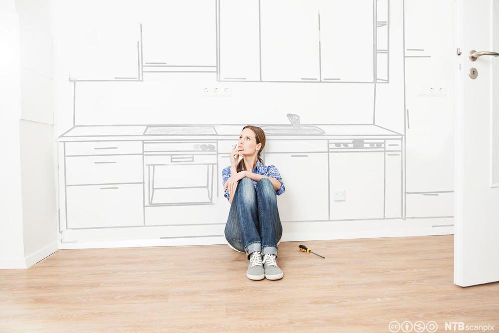 Kvinne drømmer om nytt kjøkken. Foto.