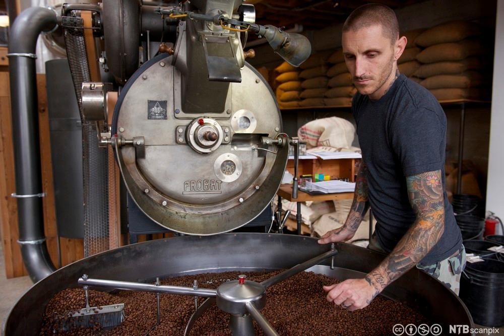 Ei arbeider sjekker kaffibønner som blir brende i ein stor maskin. Foto.