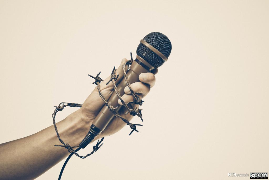 Hånd som holder mikrofon med piggtråd rundt. Foto.