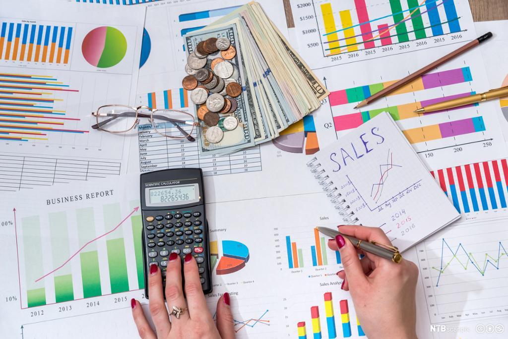 Kvinne som holder en kalkulator og ser på mange ulike grafer. Foto.