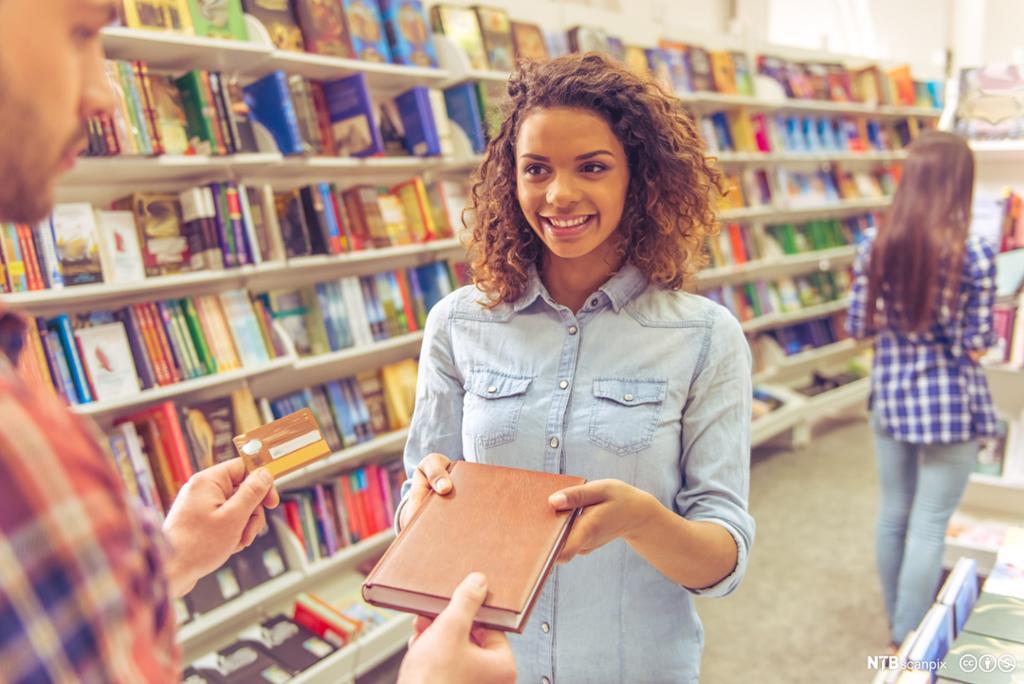 Kvinne som gir en bok til en mann med et betalingskort i hånden. Foto.