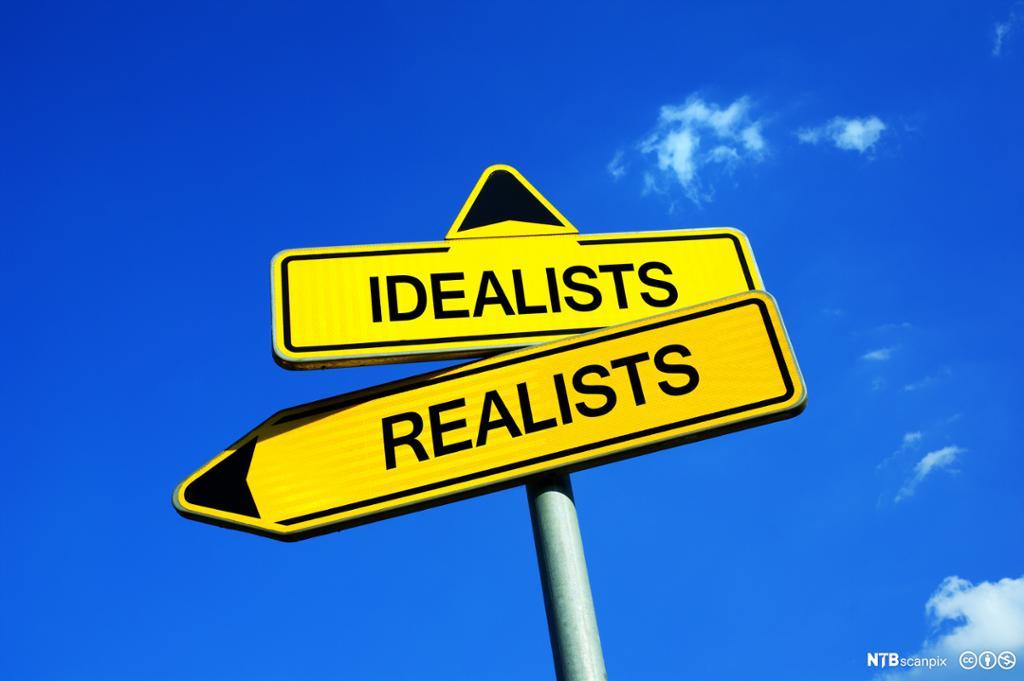 """To veiskilt med påskrift """"Realism"""" og """"Idealism"""". Det første peker mot venstre, det andre opp mot himmelen. Foto."""